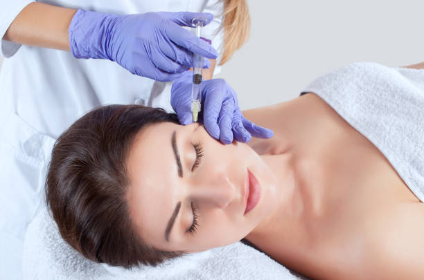 The cosmetologist performing botox for rejuvenating skin and face by tightening and smoothing wrinkles on the face